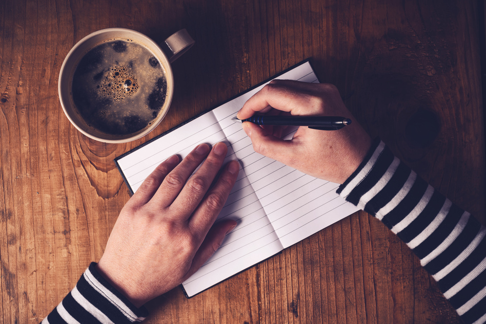 Woman drinking coffee and writing a diary note